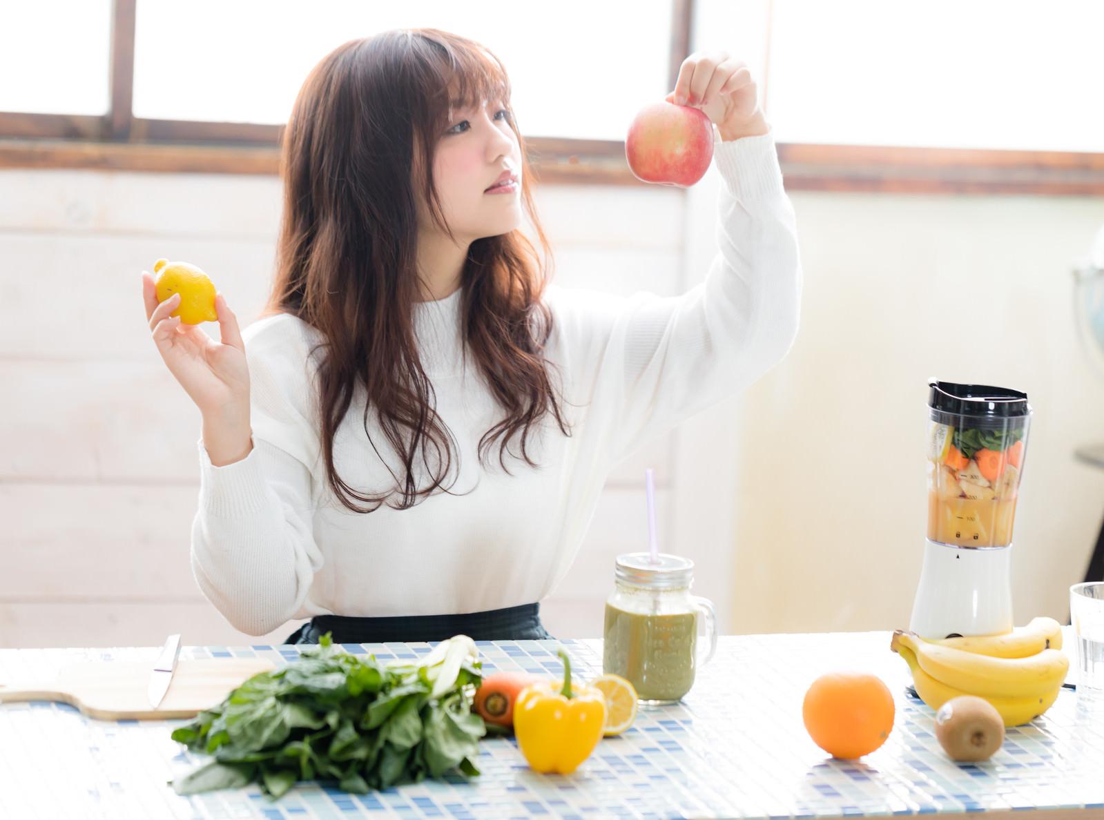 「スムージーに入れる果物(リンゴ・レモン)を選ぶ若い女性スムージーに入れる果物(リンゴ・レモン)を選ぶ若い女性」[モデル:河村友歌]のフリー写真素材を拡大