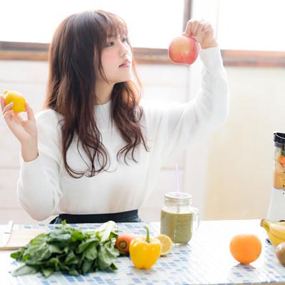 「スムージーに入れる果物(リンゴ・レモン)を選ぶ若い女性」の写真素材