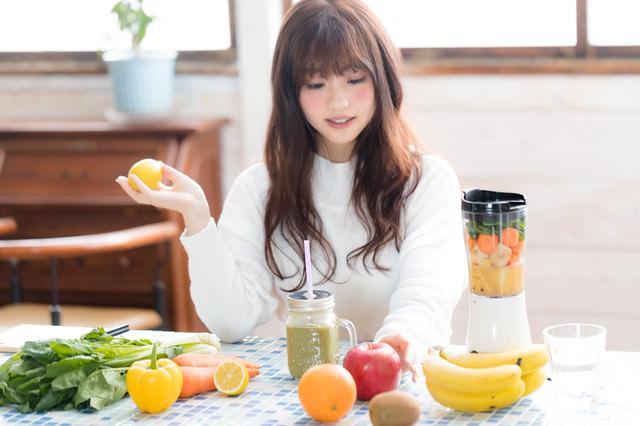 「スムージー用の果物を手に取る女性」のフリー写真素材