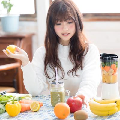「スムージー用の果物を手に取る女性」の写真素材