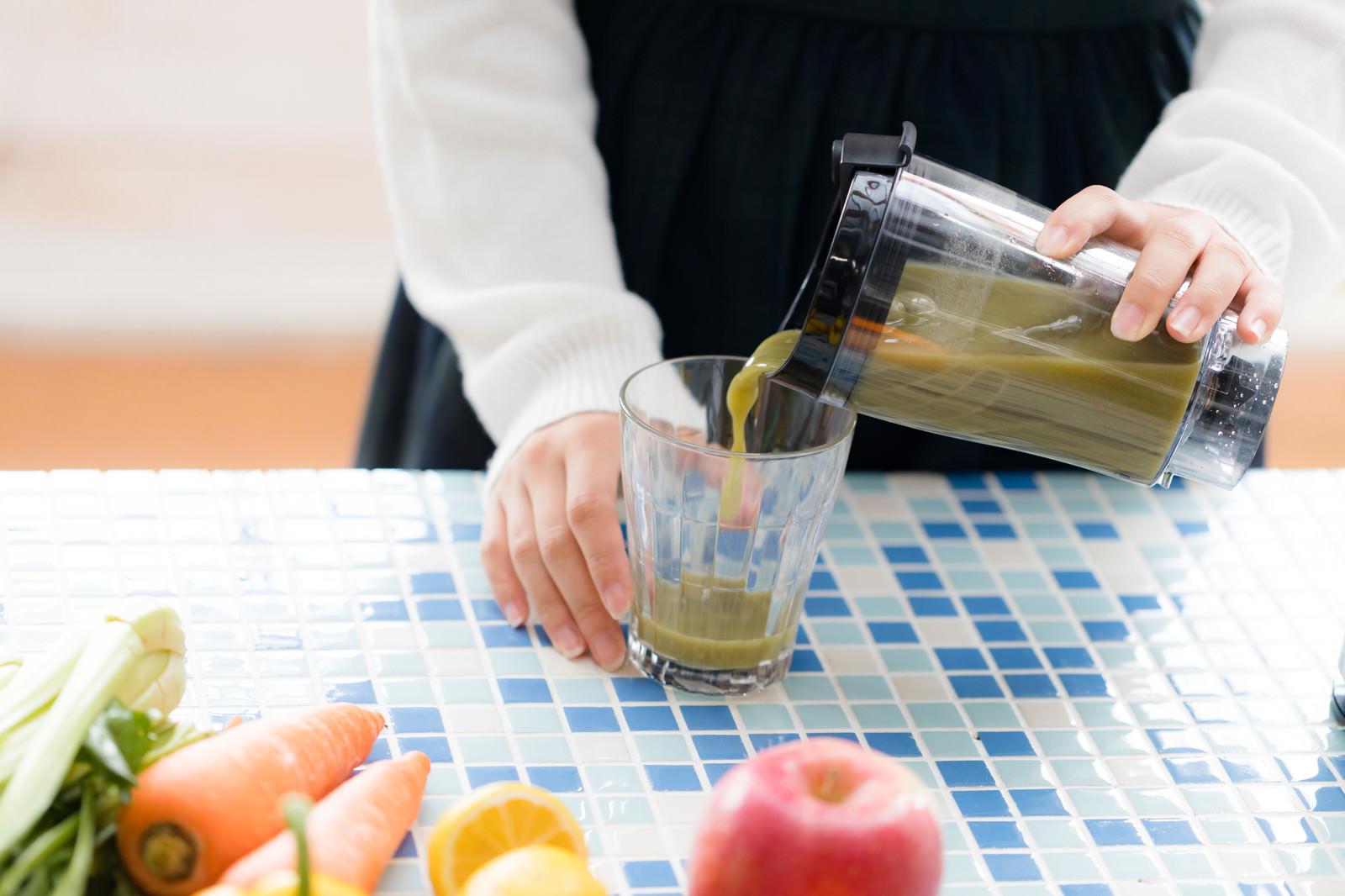 「グリーンスムージーをグラスに注ぐ」の写真