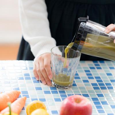「グリーンスムージーをグラスに注ぐ」の写真素材