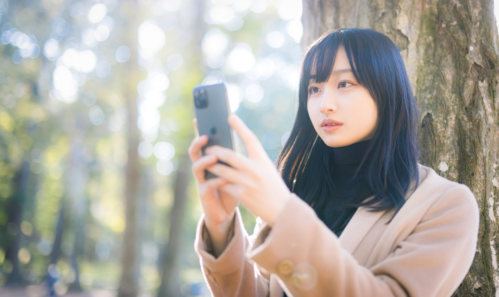 目線の高さでスマートフォンを操作する女性