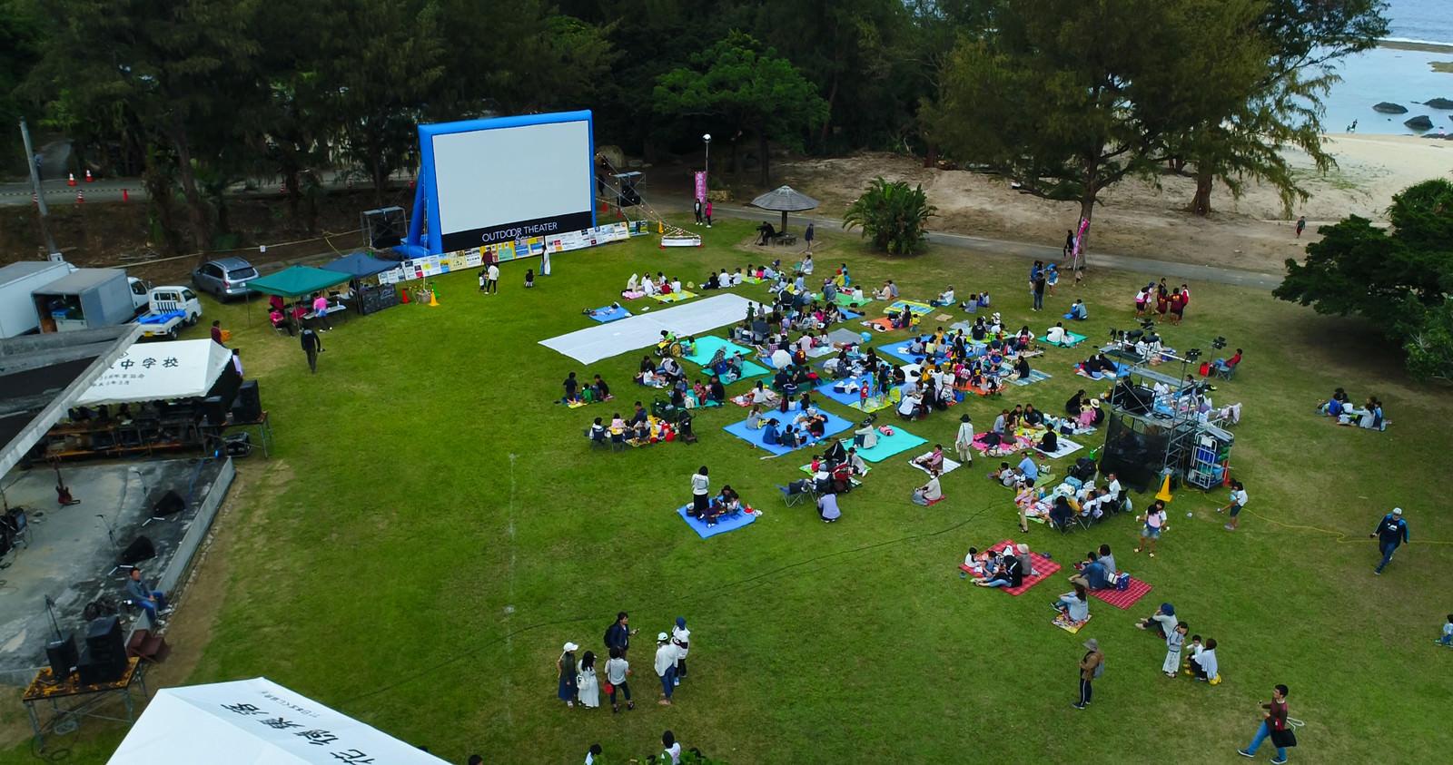 「野外映画のイベントでレジャーシートを敷いて放映を待つ人々」の写真