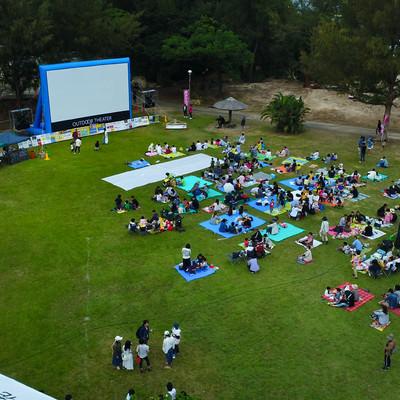 「野外映画のイベントでレジャーシートを敷いて放映を待つ人々」の写真素材