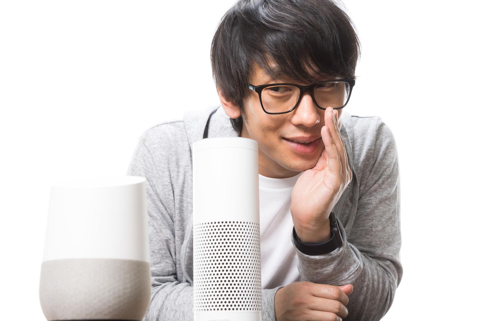 「スマートスピーカーに声をかけるメガネ男子」の写真