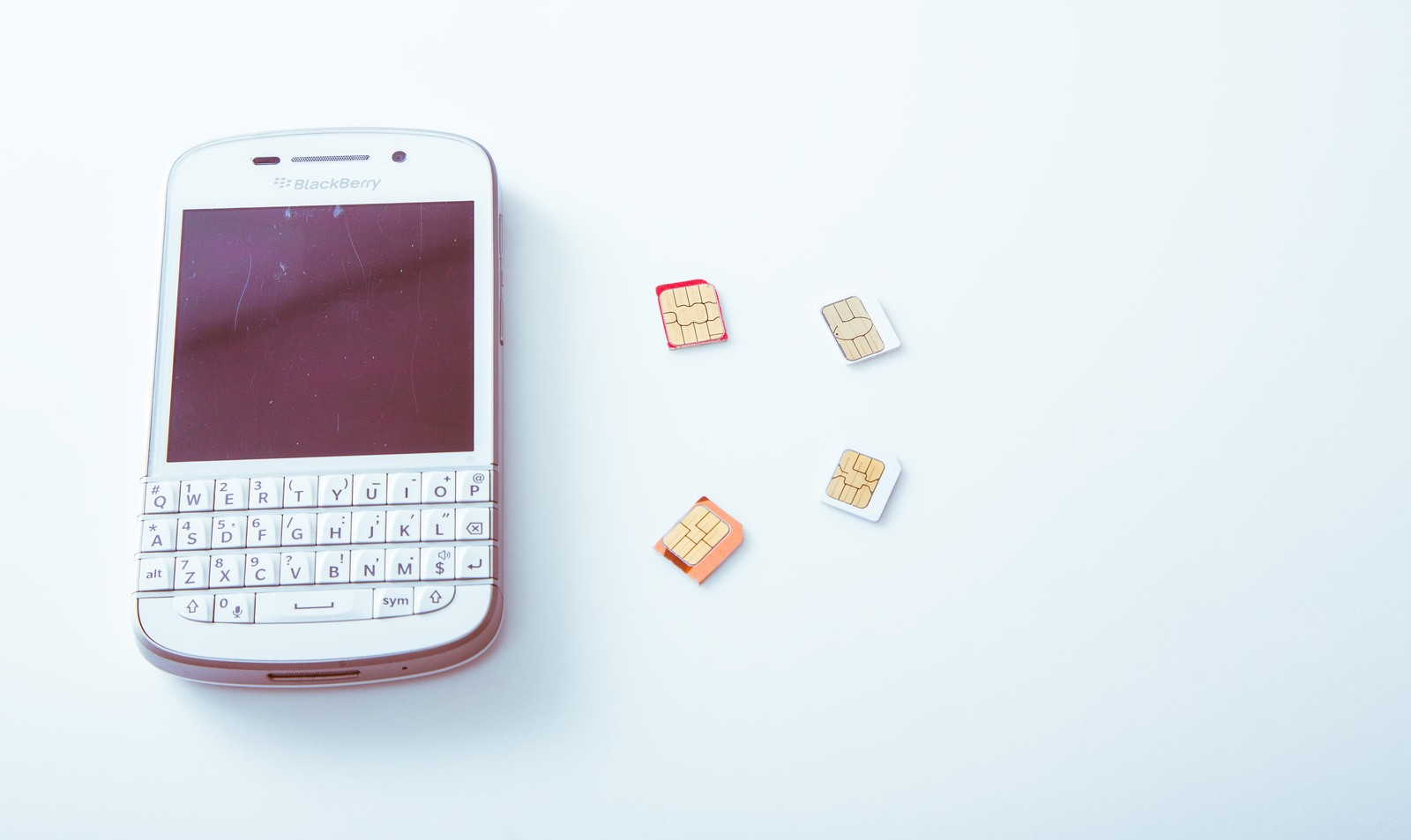 「スマートフォンと取り外したSIMカード」の写真
