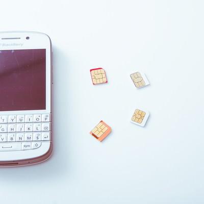 スマートフォンと取り外したSIMカードの写真