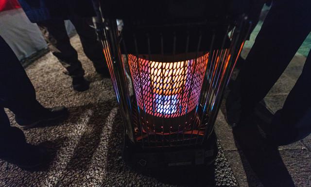 石油ストーブの周りに集まる人の足元(夜間)の写真