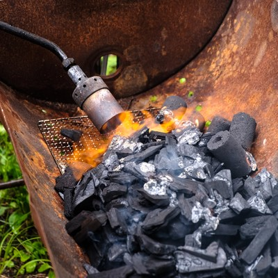 トーチバーナーで炭に火をおこすの写真
