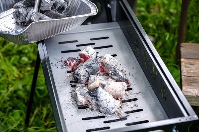 バーベキューグリルに炭を入れるの写真