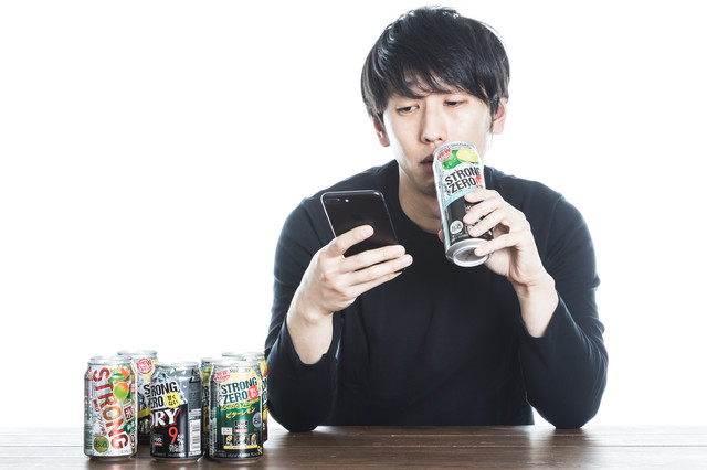 缶チューハイを飲みながら廃課金するソシャゲユーザーの写真