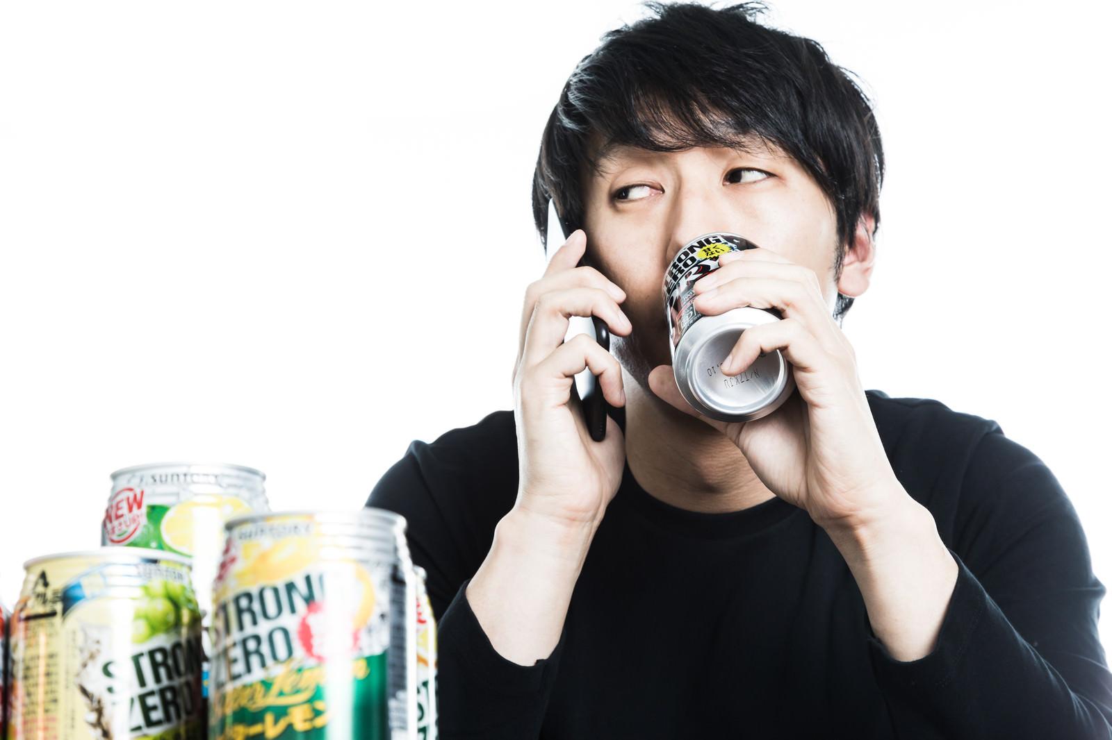 「昼間から缶チューハイを飲みながらクライアントにリスケを伝えるダメフリーランス」の写真[モデル:大川竜弥]