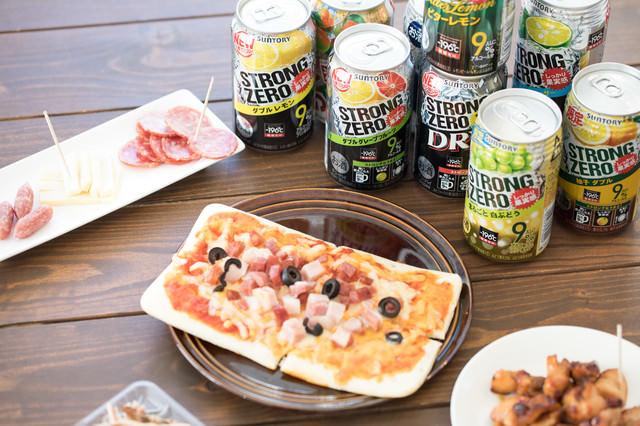 缶チューハイとピザやつまみ類の写真