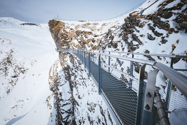 断崖雪壁に設置された吊橋の様子(スイス)の写真