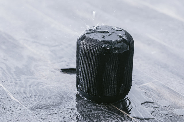 防水のワイヤレススピーカーに水をかけるの写真