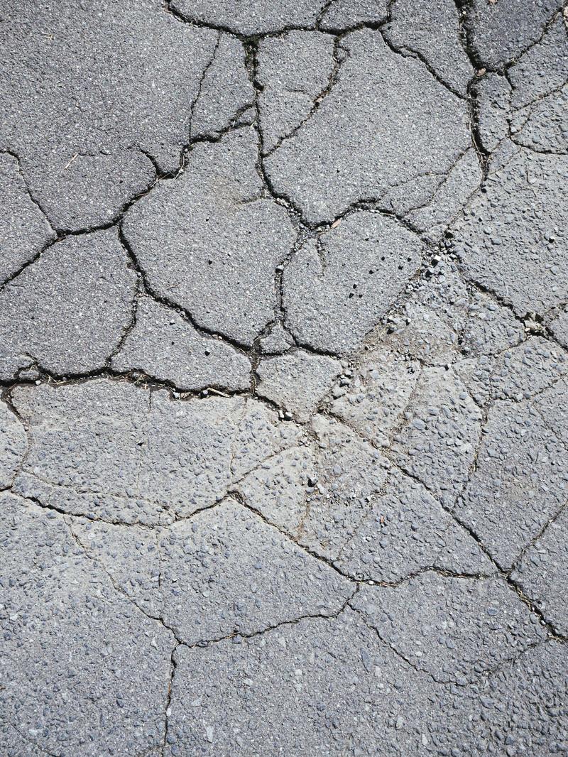 「ヒビが入ったアスファルトの地面(テクスチャ)」の写真
