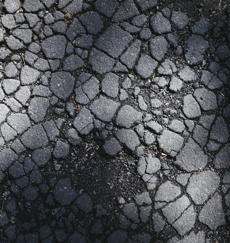 「ひび割れたアスファルトに残る影(テクスチャ)」の写真