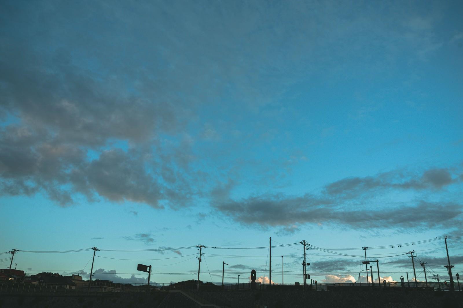 「電柱のシルエットと薄雲かかる青空」の写真