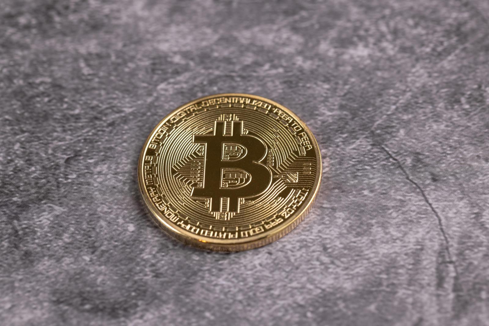 「卓上に置かれた一枚の金貨(ビットコイン)」の写真