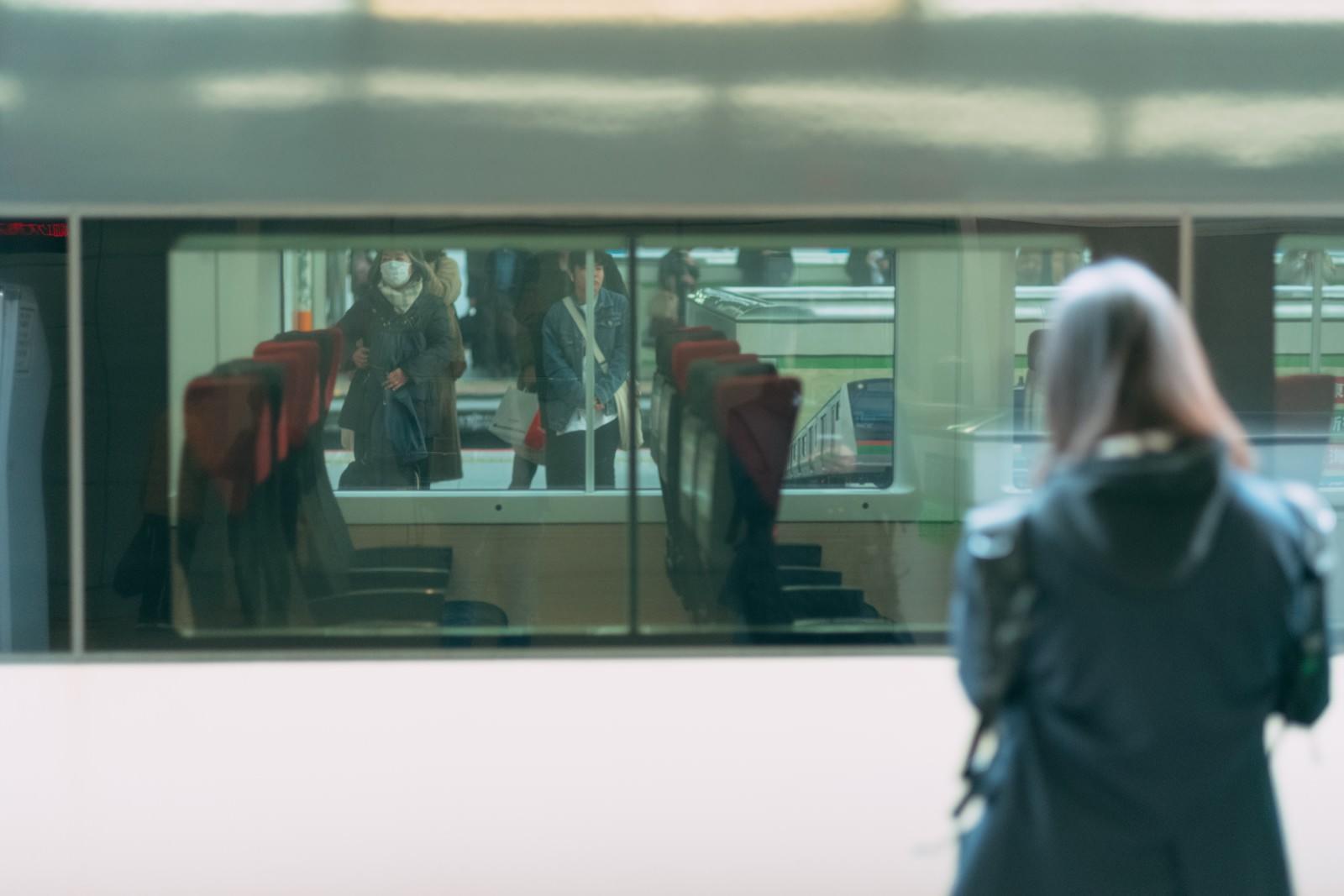 「停車中の電車越しに見る利用客」の写真
