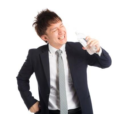 「「プハー!」暑さの中、水分補給をする会社員」の写真素材
