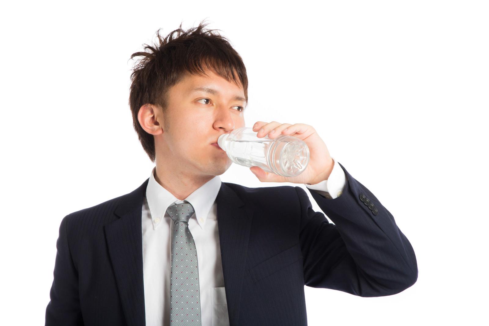「喉を潤すビジネスマン」の写真[モデル:鈴木秀]