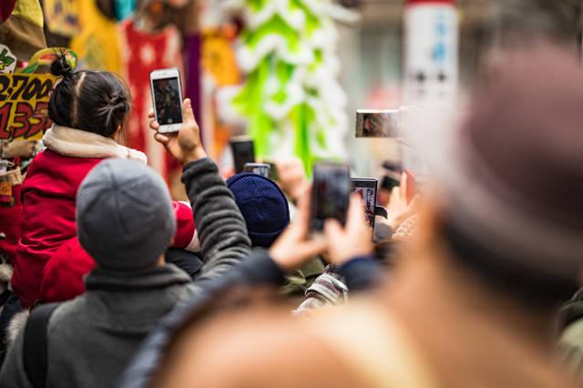 スマホを取り出して撮影しはじめる人混みの写真