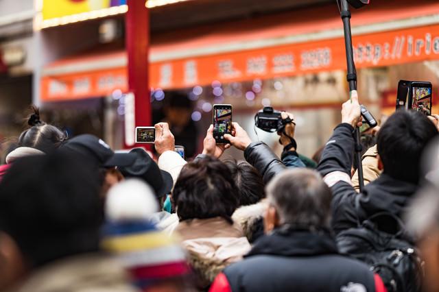 スマホで撮影する人たちの写真