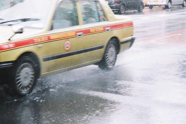 大雨で大忙しのタクシーの写真