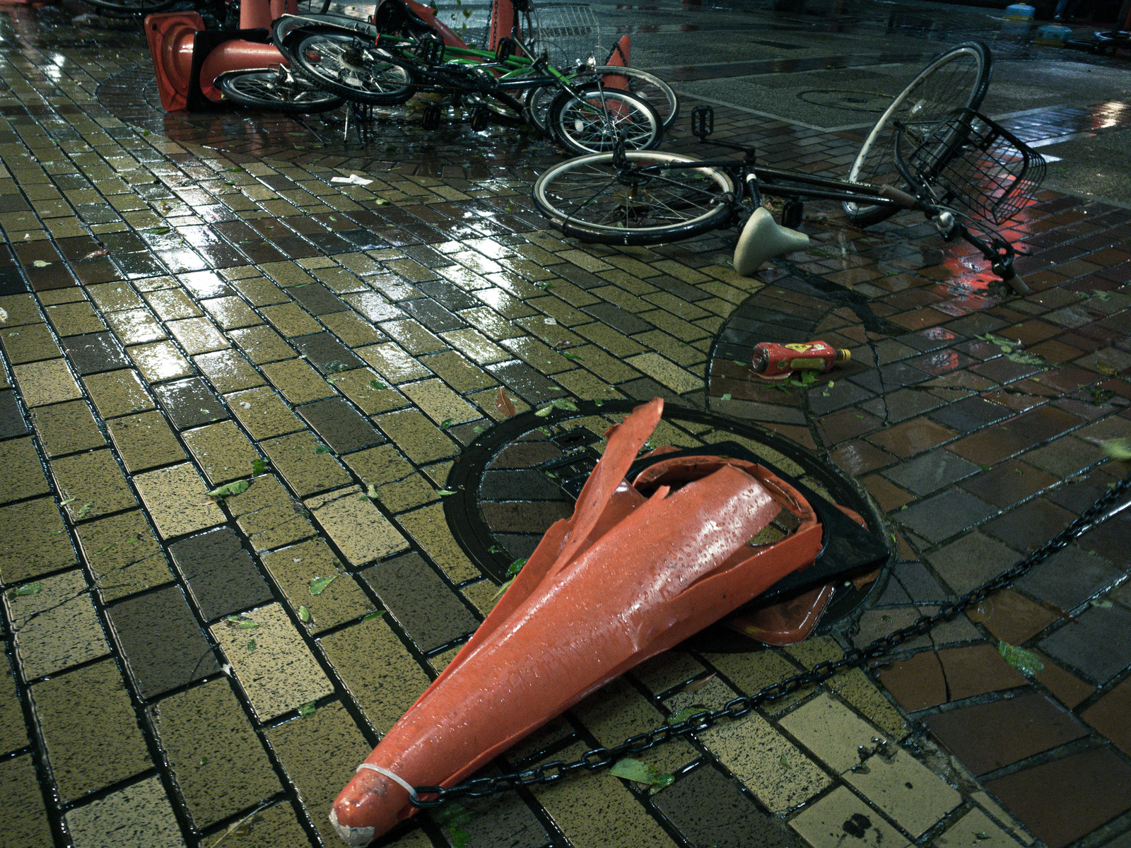 「大型の台風の後、なぎ倒されたカラーコーンと自転車」の写真