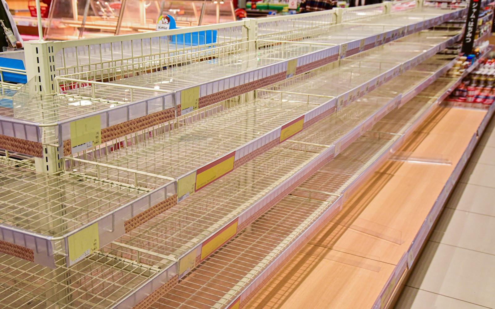 「大型の台風上陸予想でスーパーの食料品の棚が売り切れで何もない」の写真