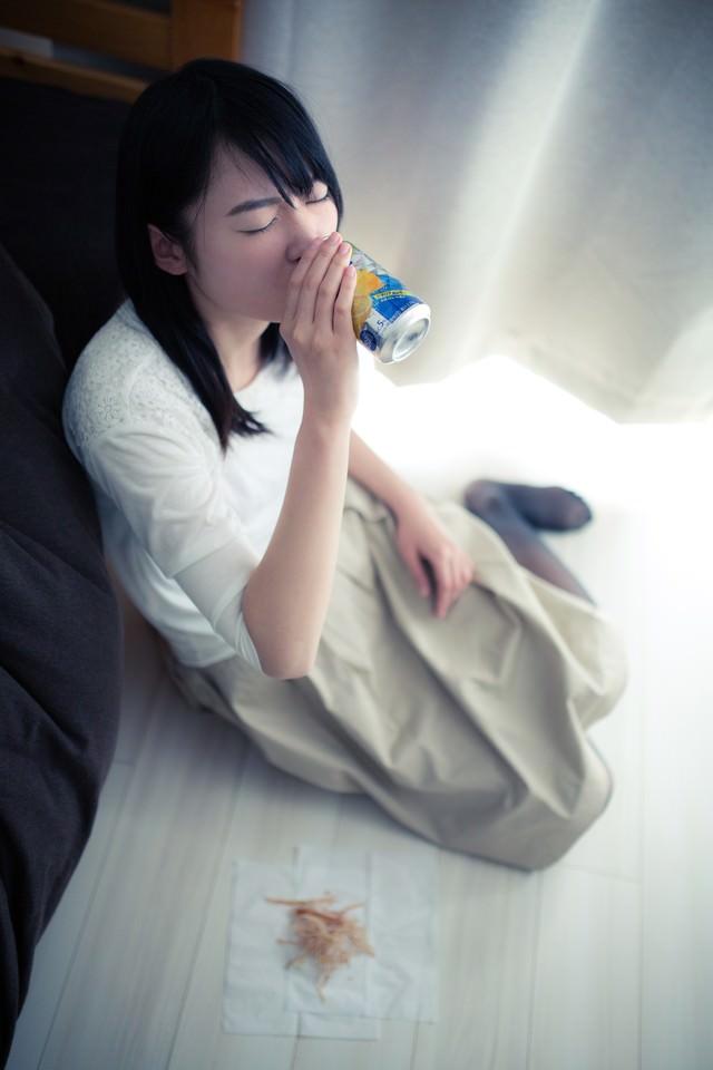お酒の力を借りる女性の写真