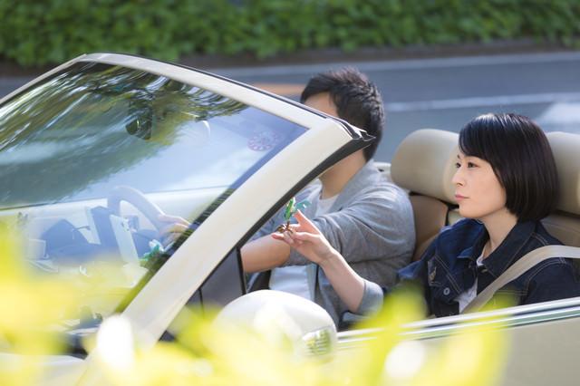 オープンカーに乗っている若い男女の写真