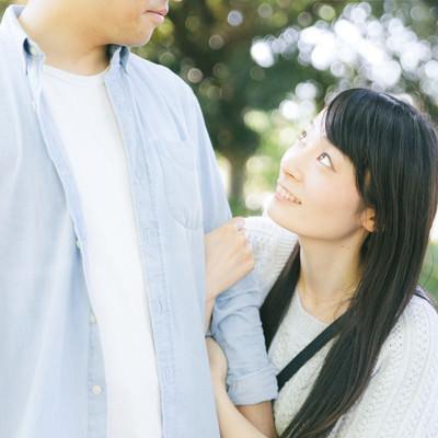 「大好きな彼の腕を掴むも顔色をうかがっちゃう彼女」の写真素材