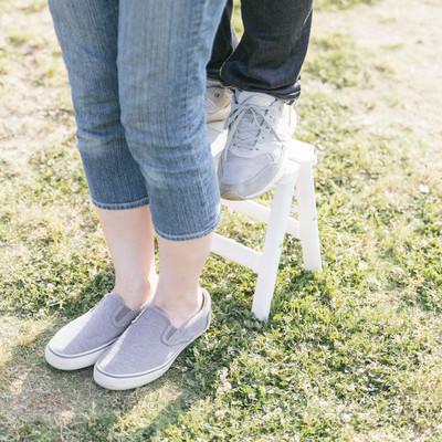 「ミニ脚立を使って「後ろからギュッ」にチャレンジする身長差カップルの足元」の写真素材