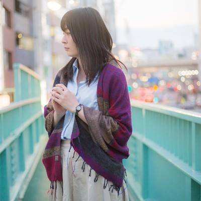 歩道橋の上で立ち止まる女性の写真