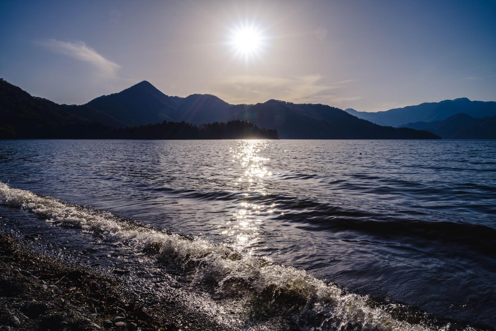 「日光中禅寺湖の沈みゆく夕陽と社山」の写真