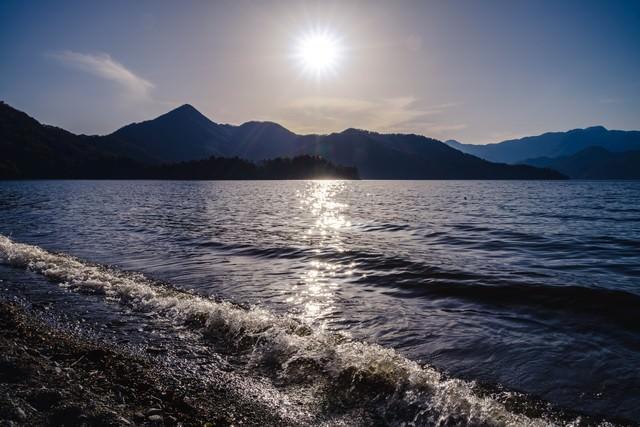 日光中禅寺湖の沈みゆく夕陽と社山の写真