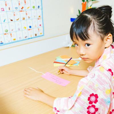 短冊に書く内容を見られまいとする娘の写真