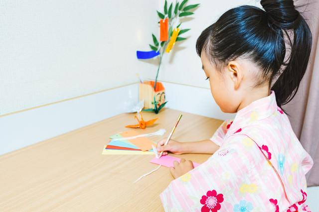 机の上で短冊に願いをこめる浴衣の女の子の写真