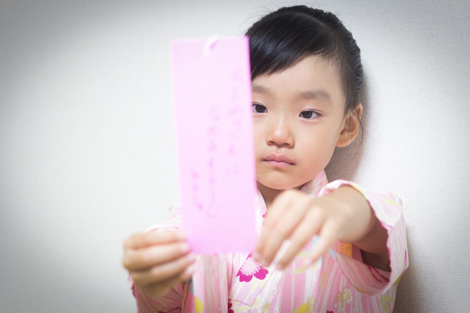 「願い事を書いた短冊が不満な女の子 | 写真の無料素材・フリー素材 - ぱくたそ」の写真[モデル:あんじゅ]