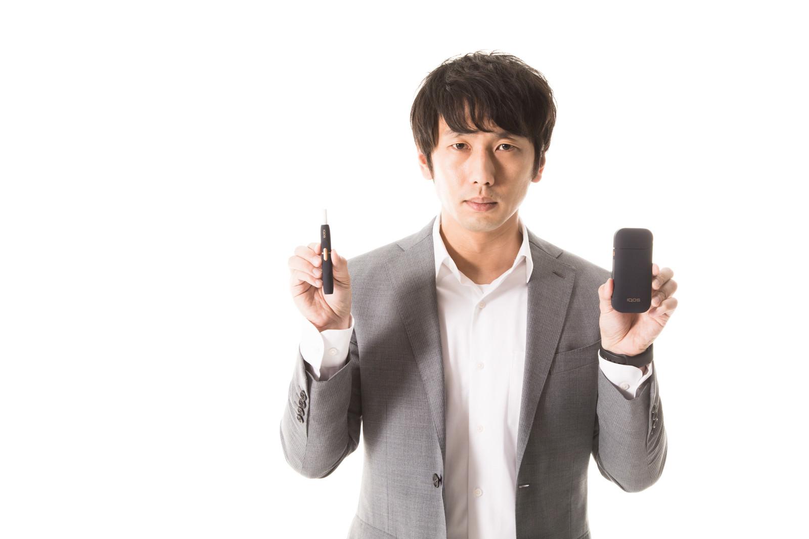 「加熱式タバコの使い方を説明する男性」の写真[モデル:大川竜弥]