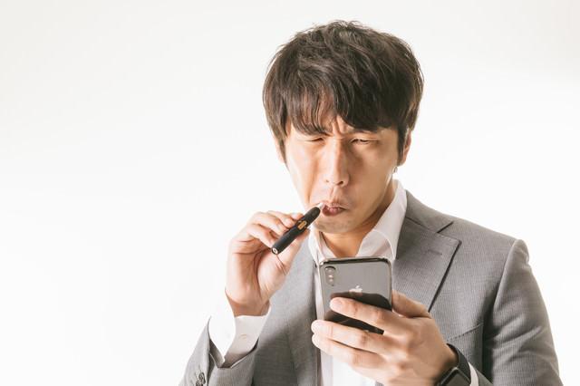 たばこ休憩中に相場をチェックする投資家