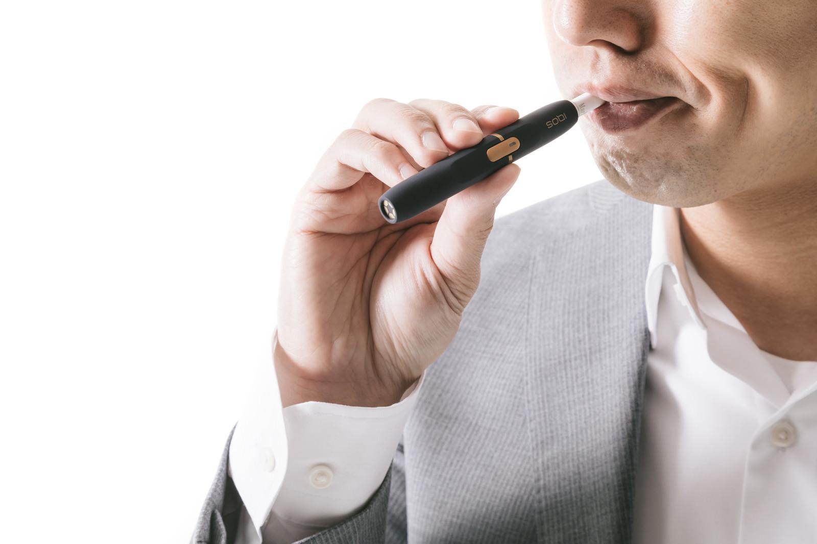 「加熱式たばこの味を確かめる男性」の写真[モデル:大川竜弥]