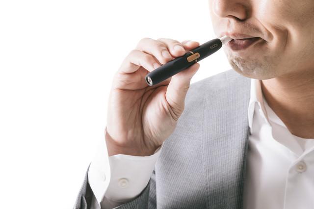 加熱式たばこの味を確かめる男性の写真