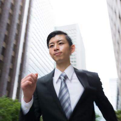 「オフィス街を走る若いビジネスマン」の写真素材