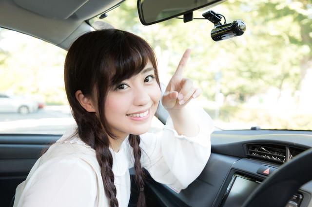 もしもの時に安心なドライブレコーダーを指さす女性の写真
