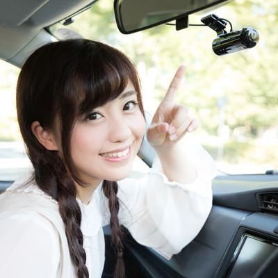 「もしもの時に安心なドライブレコーダーを指さす女性」の写真素材