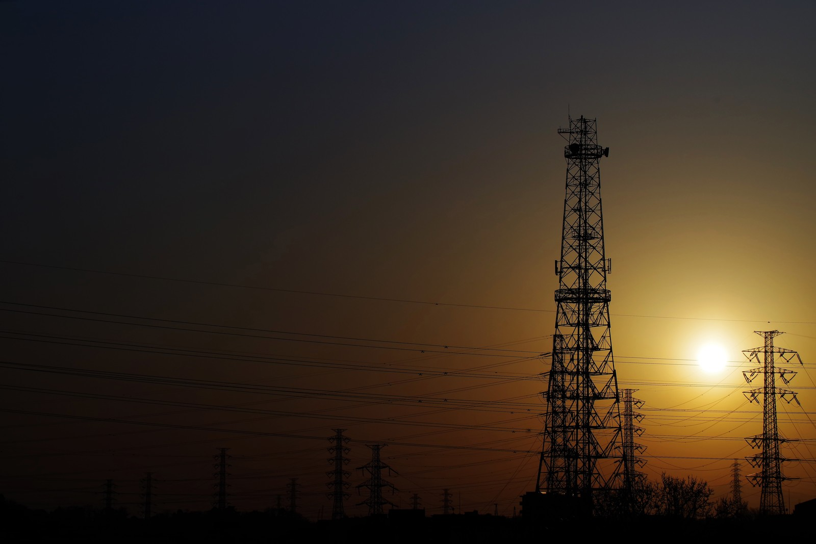 「霞む空に夕日と送電線」の写真